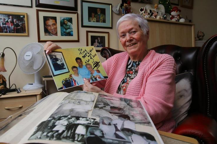 Tiny holding a photograph of herself, her sister Irene and Michael Mols.jpg