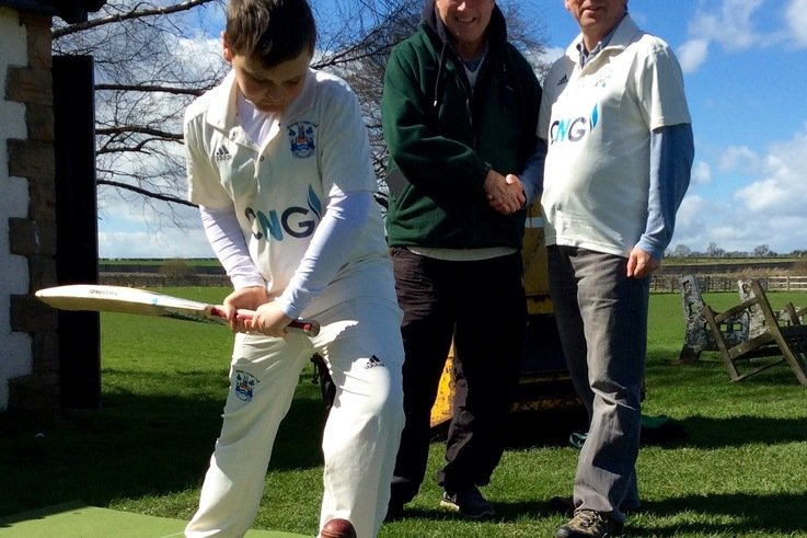 Wetherby CC's 11 year old Jack Dyson tries out the new coaching mat with Cricket Coaching Mat's David Cooper (L) and club chairman Arthur Probert (R) looking on