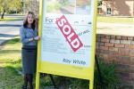 Ray White agent Deb Downey was happy to place a sold sticker on the sign at the Forbes Golf Club.