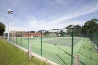 Tennis court after fence upgrade and floodlight installation