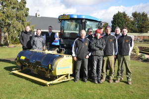 On the left of the gold painted Wiedenmann Terra Spike GXi8 are, from left, Eddie Jack and Stuart Paterson of Ernest Doe and Chas Ayres of Wiedenmann. On the right of the machine is Mick Lathrope, left, course manager at Eaton Golf Club and his greenkeeping team.