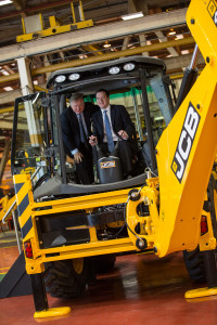 Lord Bamford (left) with the Chancellor in the cab of a JCB backhoe loader