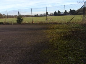 Before a disused tennis court before being transformed into new cricket practice nets by total play Ltd