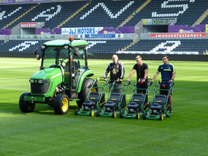 Swansea City FC grounds staff at the Liberty Stadium with the new John Deere 3720 compact tractor and cab, and four of the R54RKB walk-behind rotary mowers (left to right: groundsmen Ben Arthure & James Williams and head groundsman Dan Kirton).
